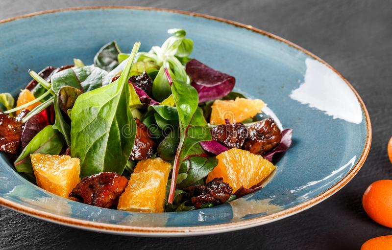 Salad with liver, arugula, orange, spinach and almonds on plate over dark stone surface. Healthy food concept. Top view.  stock image