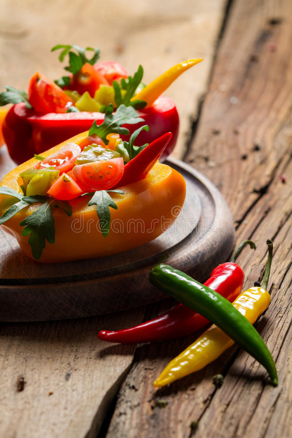 Salad made from fresh vegetables and served in bell pepper. On old wooden table stock photos