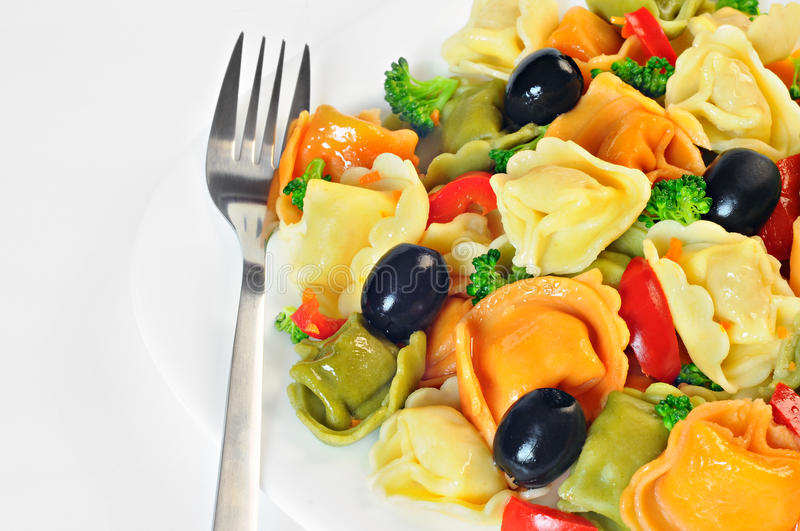 Salad made with tortellini, olives, broccoli, red pepper, on a plate royalty free stock images