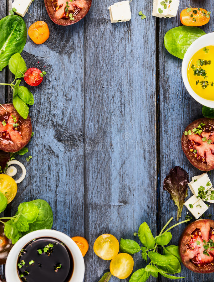 Salad making, food frame with oil,vinegar, tomatoes, basil and cheese on blue rustic wooden background, top view. Vertical stock photo