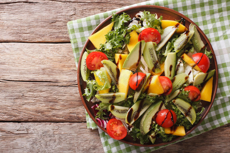 Salad of mango, avocado, kiwi, lettuce, tomato dressed with bals. Gourmet salad of mango, avocado, kiwi, lettuce, tomato dressed with balsamic sauce close-up on stock photography