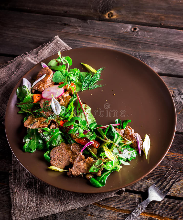 Salad with meat,greens and garden radish on brown plate. royalty free stock photo