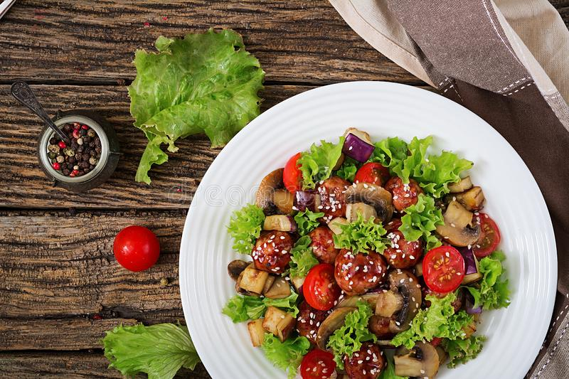Salad with meatballs, eggplant, mushrooms and tomatoes in Asian style. Healthy food. Diet meal. Top view. Flat lay stock images