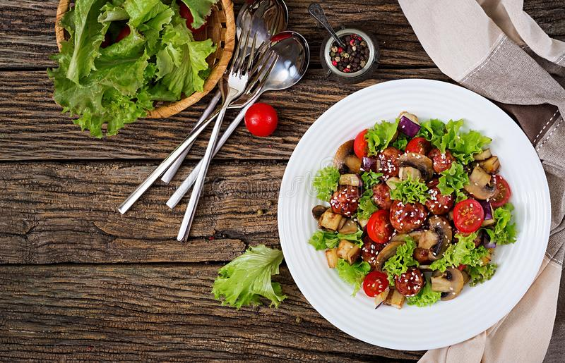 Salad with meatballs, eggplant, mushrooms and tomatoes in Asian style. Healthy food. Diet meal. Top view. Flat lay stock photo