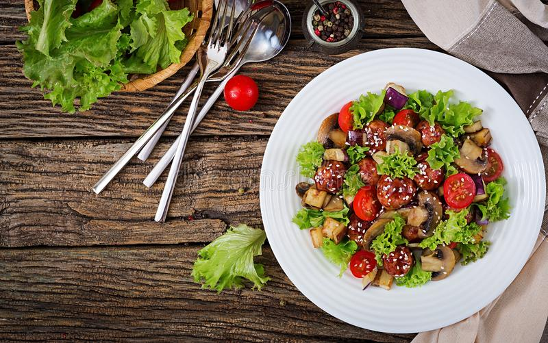 Salad with meatballs, eggplant, mushrooms and tomatoes in Asian style. Healthy food. Diet meal. Top view. Flat lay stock image