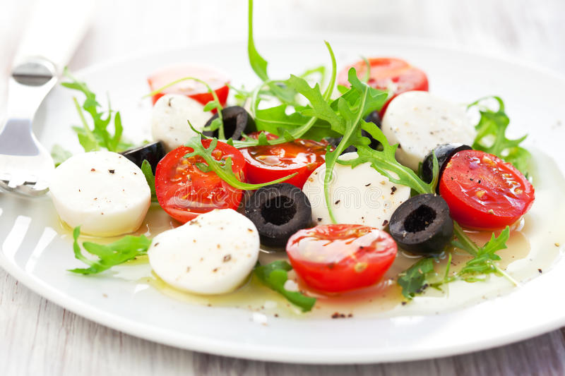 Salad with mozzarella, tomatoes and black olive. Caprese salad with mozzarella, tomatoes and black olive stock image