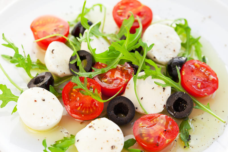 Salad with mozzarella, tomatoes and black olive. Caprese salad with mozzarella, tomatoes and black olive royalty free stock images