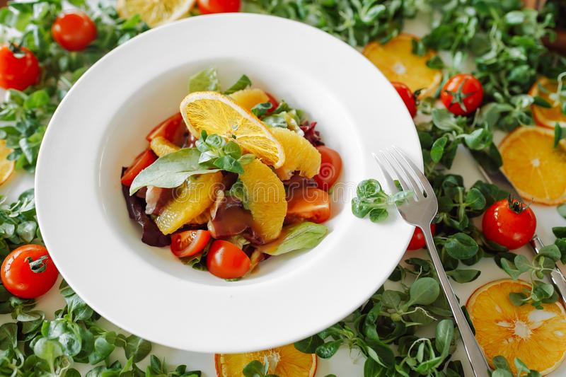 Salad in oranges, tomatoes and bacon stock photo