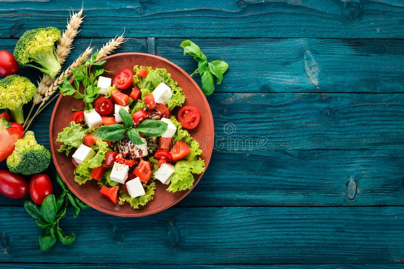 Salad in a plate. Feta cheese, cherry tomatoes, paprika, lettuce. Healthy food. On a blue wooden table table. royalty free stock images