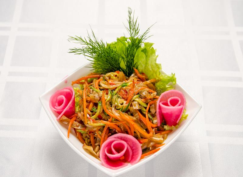 Salad of pork ears, carrots, Bulgarian pepper, fresh cucumbers, lettuce, onions and greens seasoned with vegetable oil royalty free stock photos