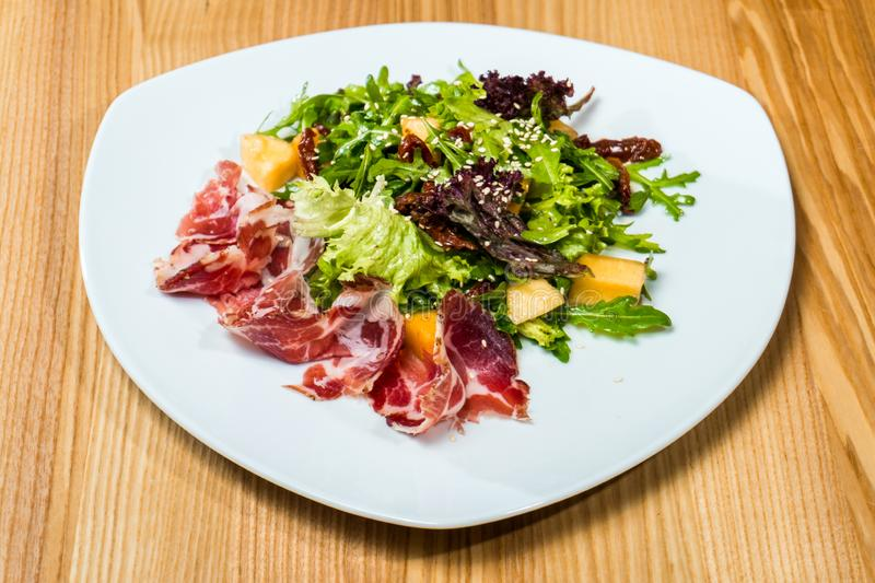 Salad with prosciutto and mango in a white plate royalty free stock photography