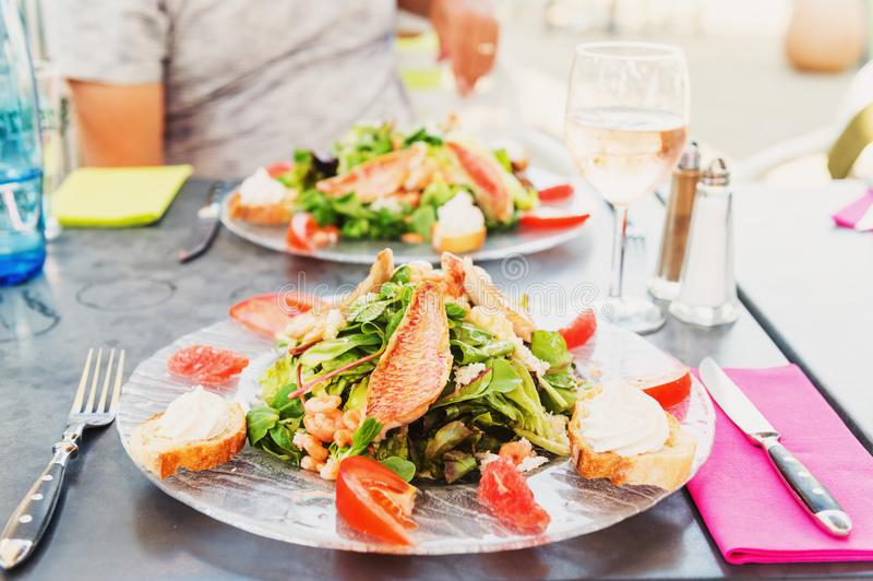 Salad provencal with red grilled snapper stock photos