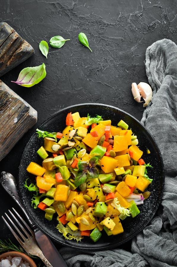 Salad of pumpkin, avocado and pumpkin seeds. royalty free stock image
