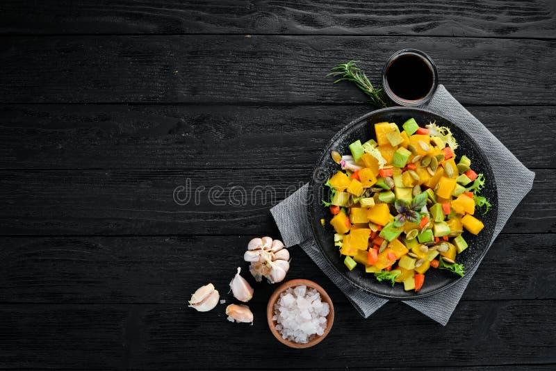 Salad of pumpkin, avocado and pumpkin seeds. royalty free stock photo