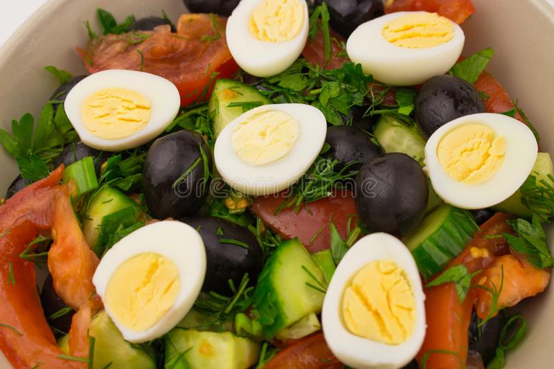 Salad with quail eggs tomato cucumber olive sliced vegetables halves of small eggs close-up stock image