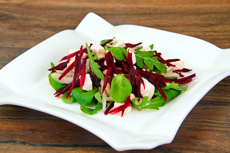 Salad of raw beets, pears, arugula, roots. Sunflower seeds and cheese Studio Photo stock image