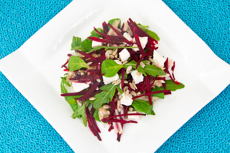 Salad of raw beets, pears, arugula, roots. Sunflower seeds and cheese Studio Photo royalty free stock images