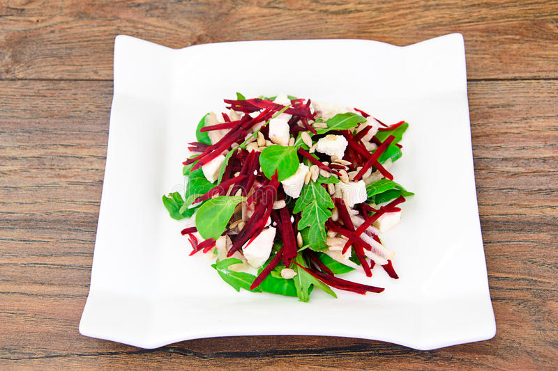 Salad of raw beets, pears, arugula, roots. Sunflower seeds and cheese Studio Photo royalty free stock photography