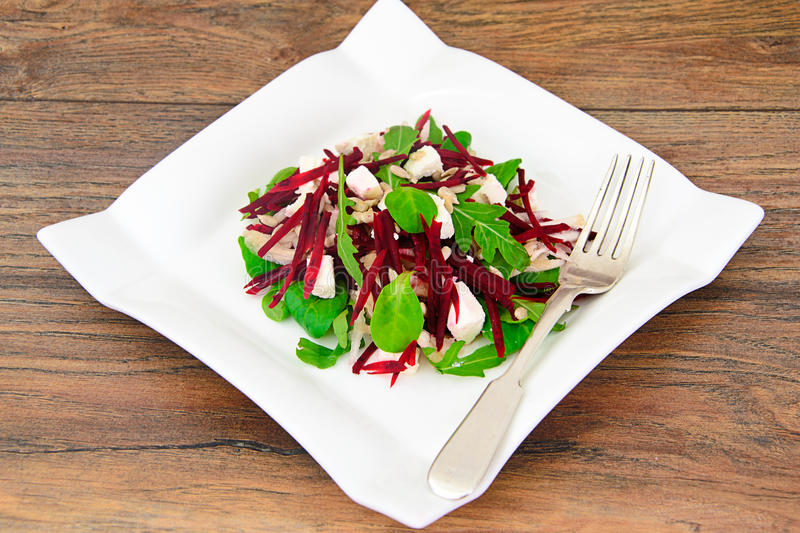 Salad of raw beets, pears, arugula, roots. Sunflower seeds and cheese Studio Photo royalty free stock photos