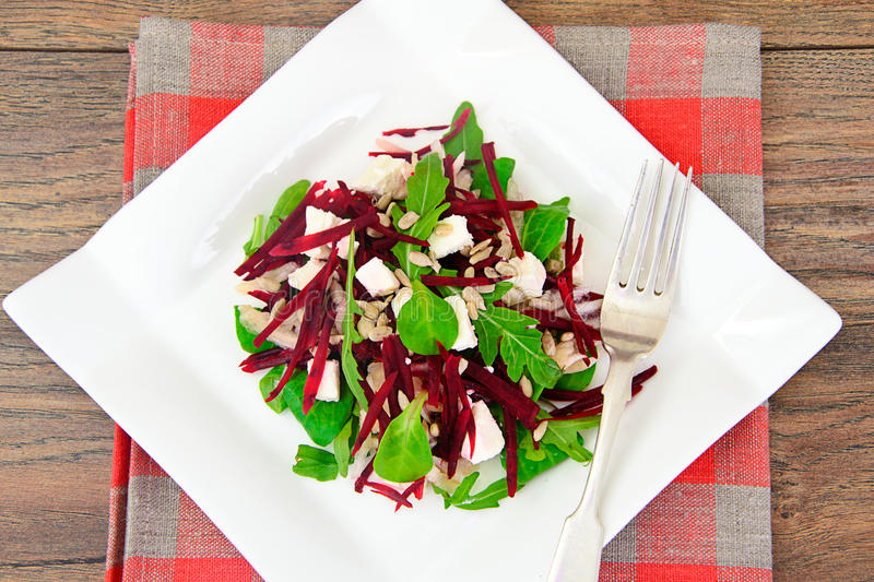 Salad of raw beets, pears, arugula, roots. Sunflower seeds and cheese Studio Photo stock photography