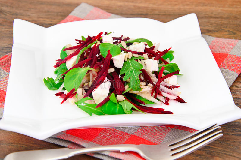 Salad of raw beets, pears, arugula, roots. Sunflower seeds and cheese Studio Photo royalty free stock image
