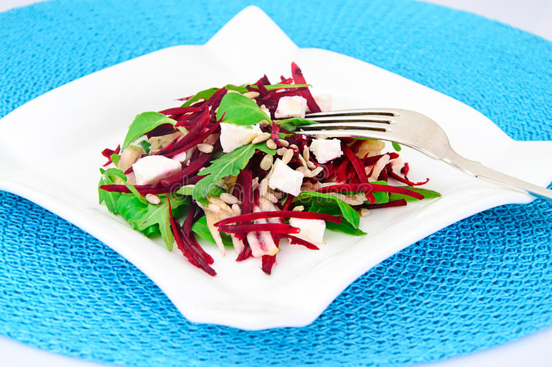 Salad of raw beets, pears, arugula, roots. Sunflower seeds and cheese Studio Photo royalty free stock photo