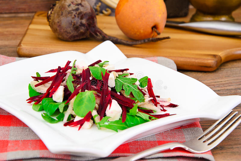 Salad of raw beets, pears, arugula, roots. Sunflower seeds and cheese Studio Photo stock photo