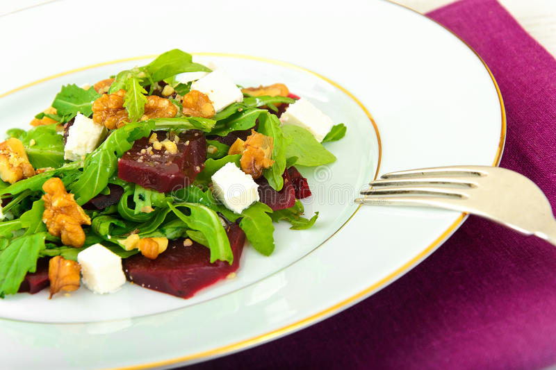Salad of Raw Beets, Pears, Arugula, Roots. Sunflower Seeds and Cheese. Studio Photo stock photography