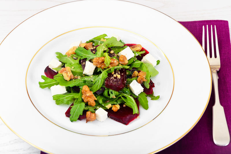 Salad of Raw Beets, Pears, Arugula, Roots. Sunflower Seeds and Cheese. Studio Photo stock photo