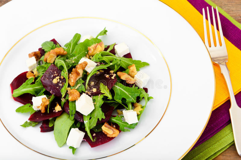 Salad of Raw Beets, Pears, Arugula, Roots. Sunflower Seeds and Cheese. Studio Photo stock photos