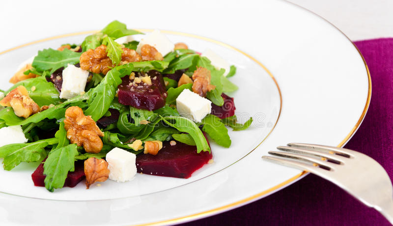 Salad of Raw Beets, Pears, Arugula, Roots. Sunflower Seeds and Cheese. Studio Photo stock images