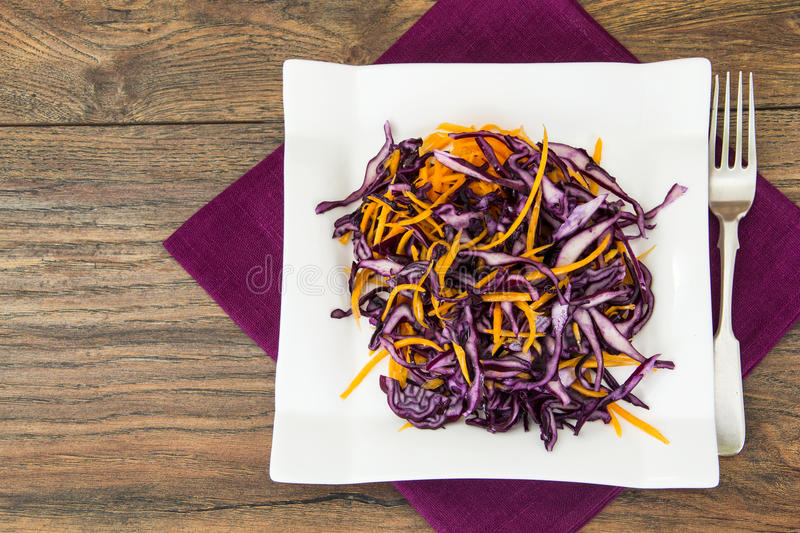 Salad of red cabbage and carrots on white plate. Studio Photo royalty free stock photography