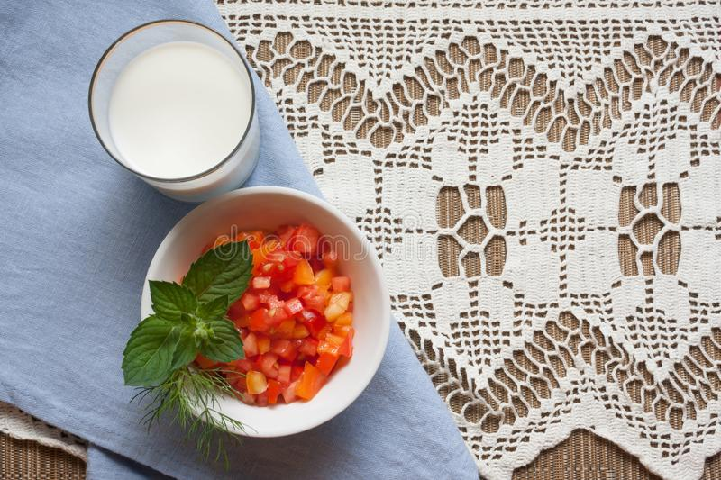 Salad of red tomatoes and orange bell peppers with a bunch of mint and dill with glass of milk on rustic background with copy spac. E. Background for a healthy stock photos