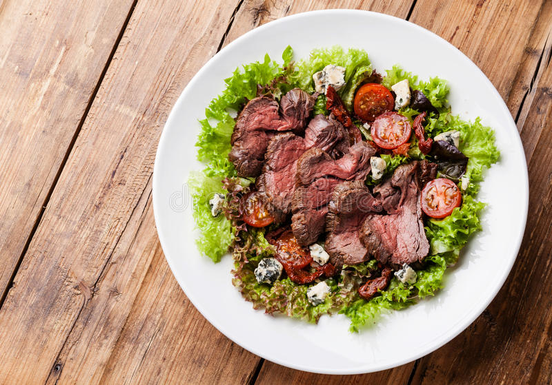 Salad with roast beef. Salad leaves with sliced roast beef and sun-dried cherry tomatoes on wooden background stock image