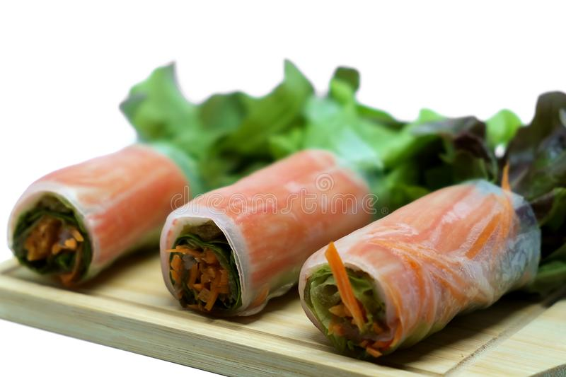 Salad roll in noodle with carrot and fresh vegetables on wooden plate and white background stock image
