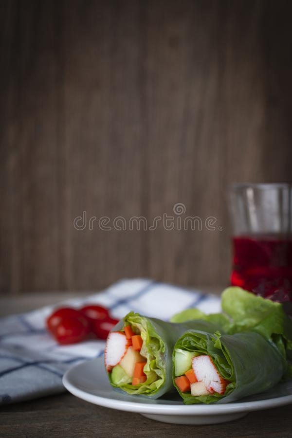 Salad rolls on white plate placed on a wooden table with White Blue Striped Fabric, tomato and red water in glass placed backside royalty free stock photography