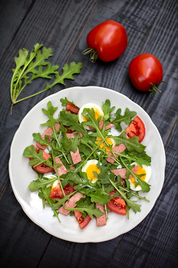 Salad with rucola, tomato, eggs and ham royalty free stock photography