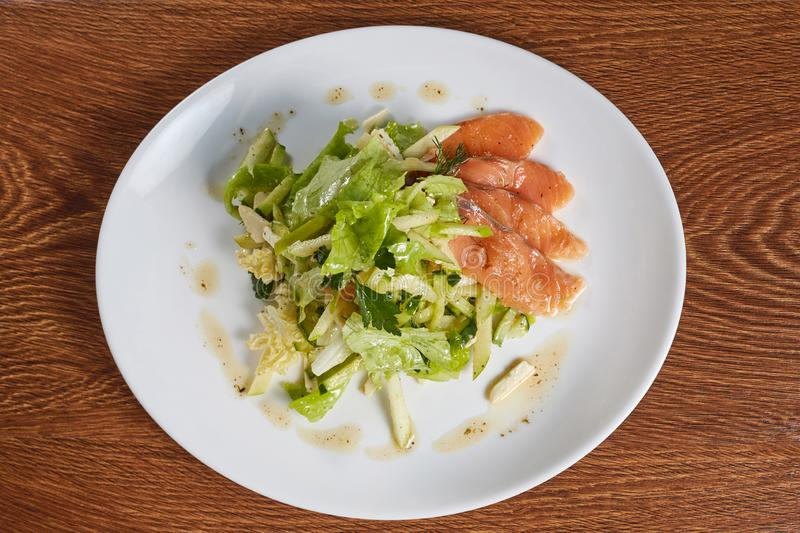 Salad of salmon, lettuce, chopped apples, parsley and dill, drizzled with olive oil mixed with ground red pepper. Close up, flat lay, top view stock images