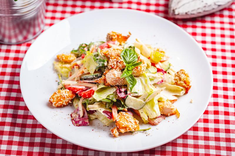 Salad with salmon, vegetables and mixed greens on white plate stock images
