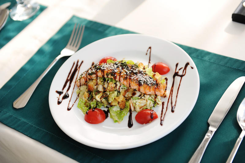 Salad with salmon on a white plate. Served on a table with a green tablecloth in a restaurant. Salad with salmon, tomatoes, herbs, sesame seeds on a white plate stock photography