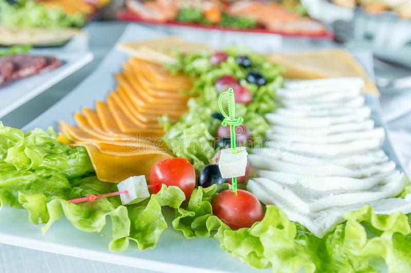Salad with sausage, greens and other on table with white table. Catering concept. stock image