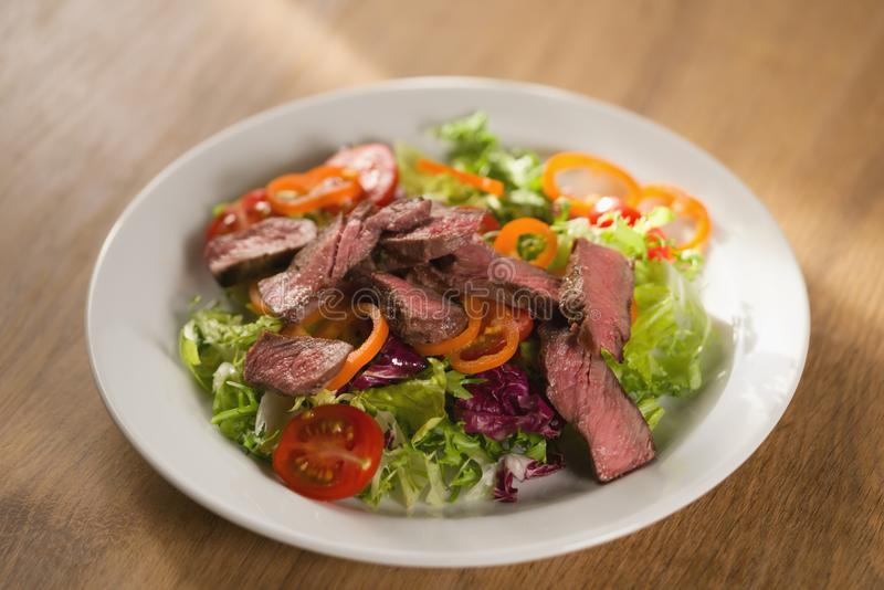 Salad with sliced filet mignon steak. On wood table stock photography