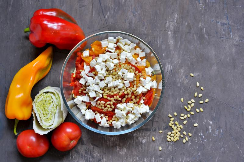 Salad slicing of red and yellow sweet peppers, tomatoes sprinkled with pine nuts and cubes of feta cheese. stock images