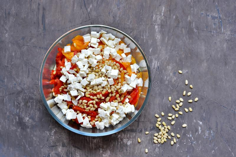 Salad slicing of red and yellow sweet peppers, tomatoes sprinkled with pine nuts and cubes of feta cheese. stock photos