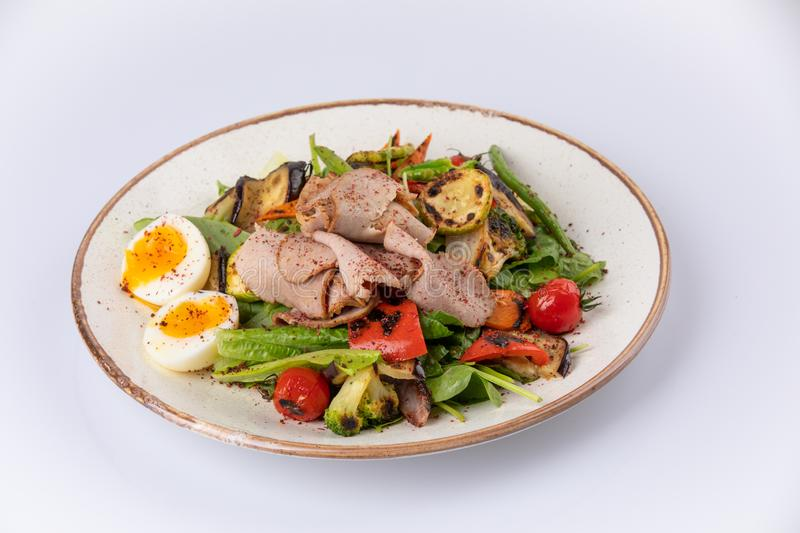 Salad with Strips of roast beef, eggs and grilled vegetables stock photos