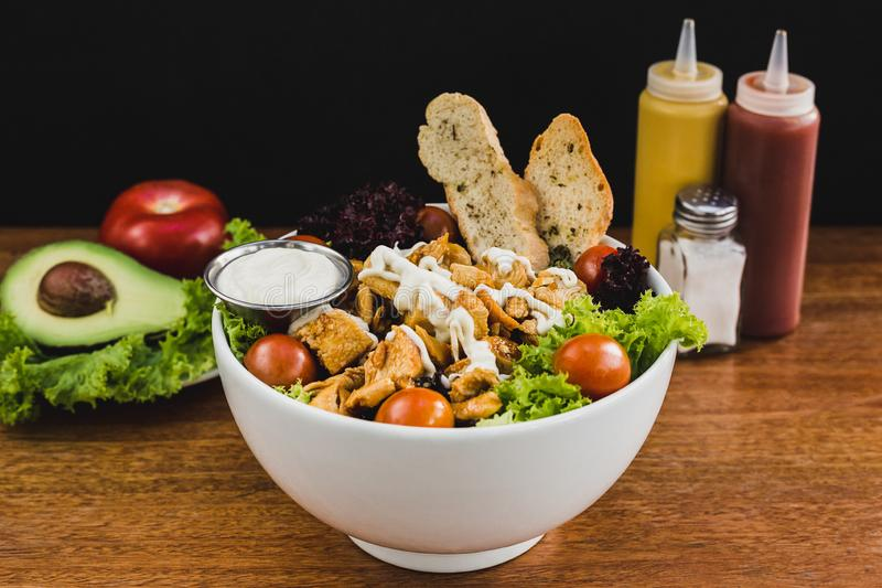 Salad with teriyaki chicken, lettuce, cherry tomato and garlic sauce stock photos