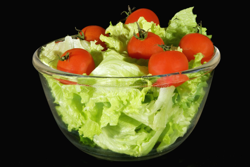 Salad and tomatoes. Green salad and red tomatoes in a transparent bowl stock photos
