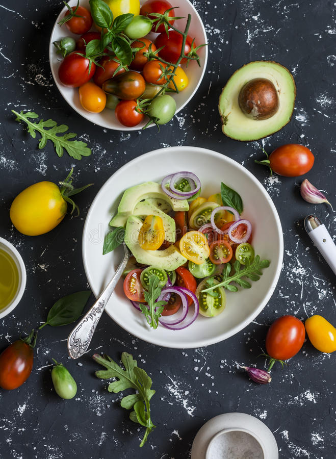 Salad with tomatoes and avocado on a dark background. royalty free stock image