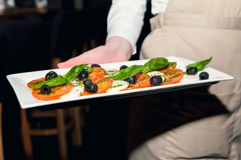 Salad of tomatoes basil and basil olives on a white rectangular plate in the hands of the waiter close up stock image
