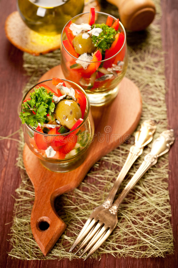 Salad of tomatoes, cucumbers, olives, peppers and blue cheese with olive oil stock images
